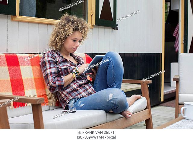 Mid adult woman using digital tablet on cabin porch