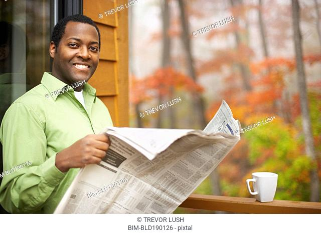 African man reading newspaper outdoors