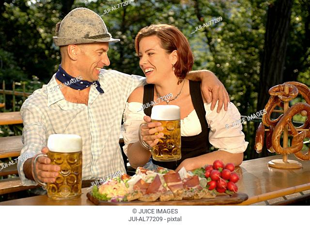 View of a young couple drinking beer in a beergarden, Munich, Bavaria, Germany