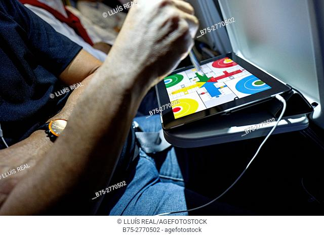 Airplane passenger playing parchis in a digital tablet