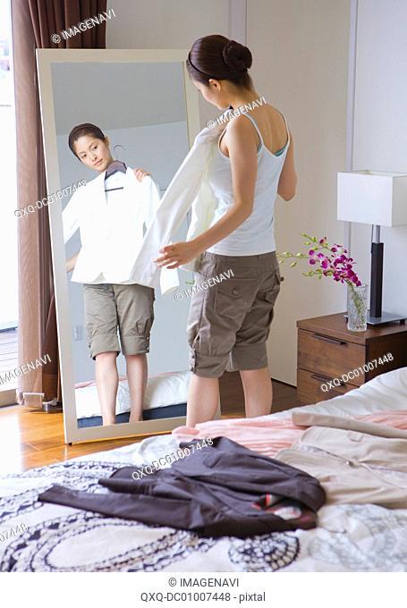 Woman in bedroom choosing clothes