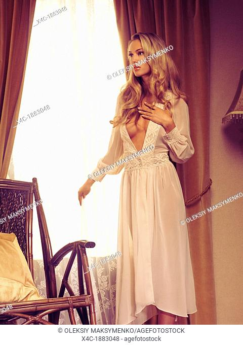 Beautiful young woman with long blond hair wearing a white night gown standing by the window