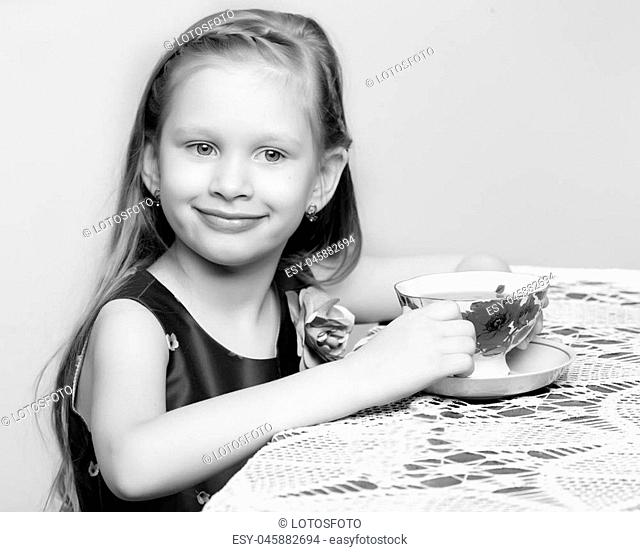 A beautiful little girl with long blond hair sitting at a table and drinking tea.Black and white photography