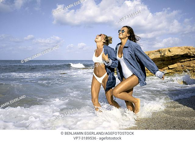 Two women running in sea water at beach, Chersonissos, Crete, Greece