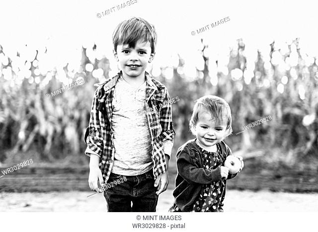 Two children standing side by side, brother and sister by a field of corn plants