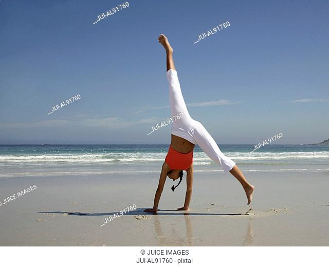 Woman performing handstand on beach