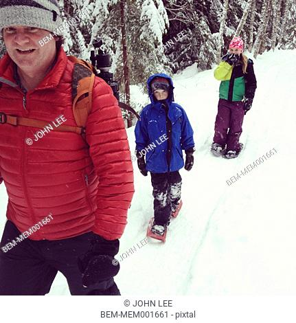 Caucasian family snow shoeing in snowy landscape