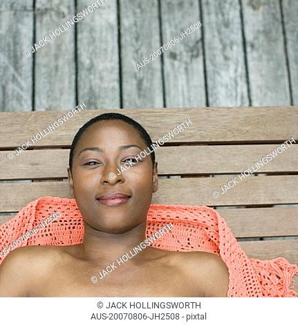 Portrait of a mid adult woman smiling and lying on wooden floor