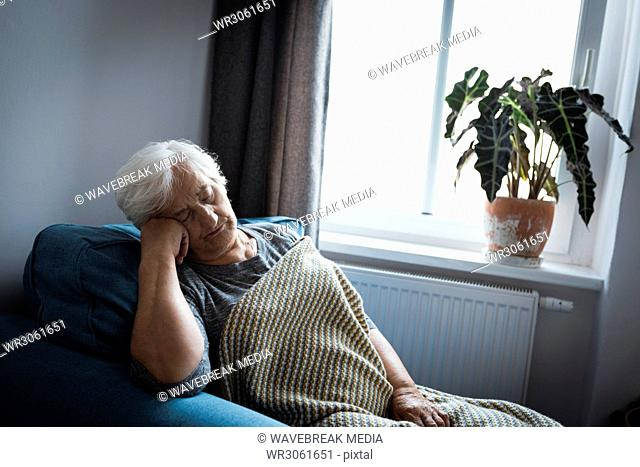 Senior woman relaxing on arm chair in living room