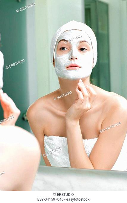 young beautiful woman with a mask on her face looks at herself in the bathroom mirror