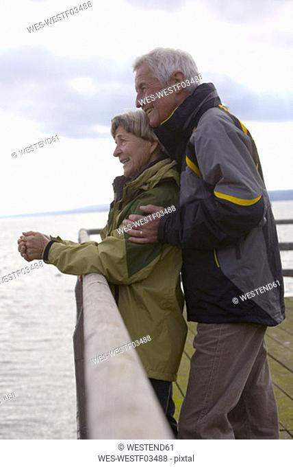 Senior couple standing on jetty, side view