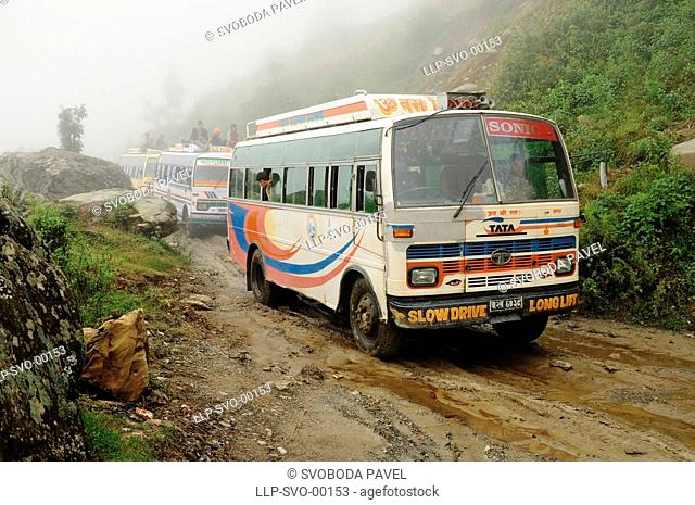 Old indian buses on poor muddy road in mountain, Himalaya, Nepal