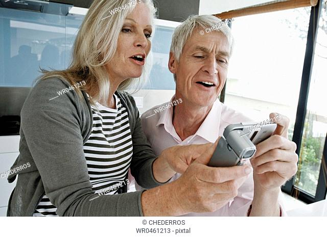 Close-up of a senior couple taking a picture of themselves with a mobile phone