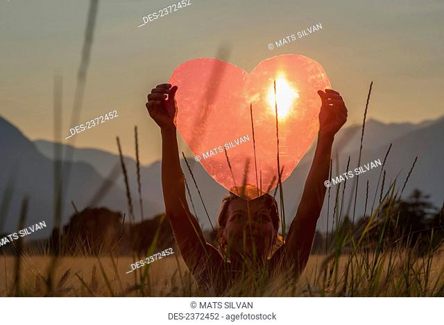 A Woman Holds Up A Red Heart With The Sun To Shine Through; Locarno, Ticino, Switzerland