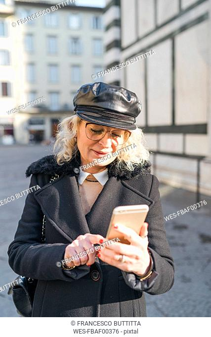 Italy, Florence, portrait of mature woman wearing black coat and leather cap using smartphone