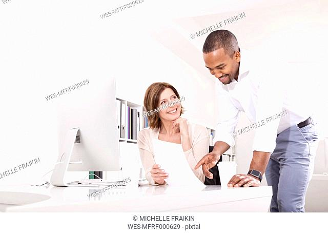 Two colleagues discussing document in an office