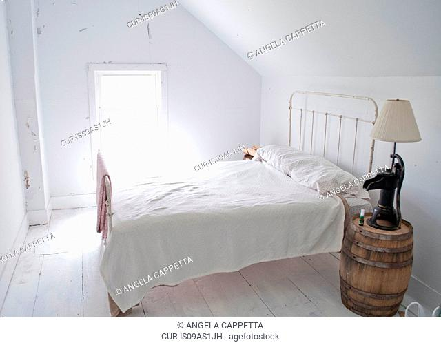 White bedroom with bed and barrel side table