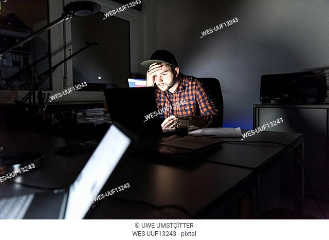 Portrait of freelancer sitting at desk working on laptop at night