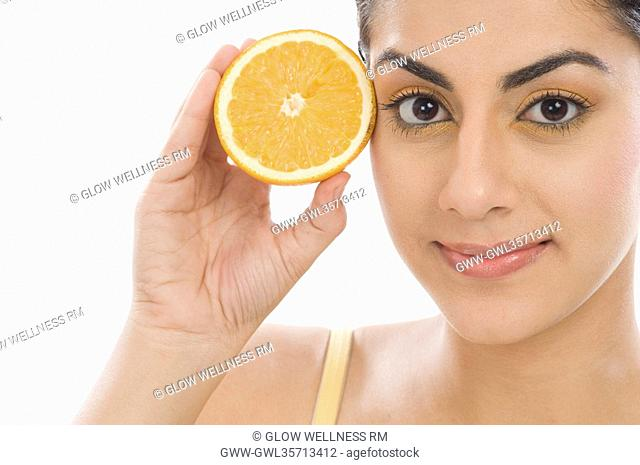 Portrait of a woman holding a half of orange