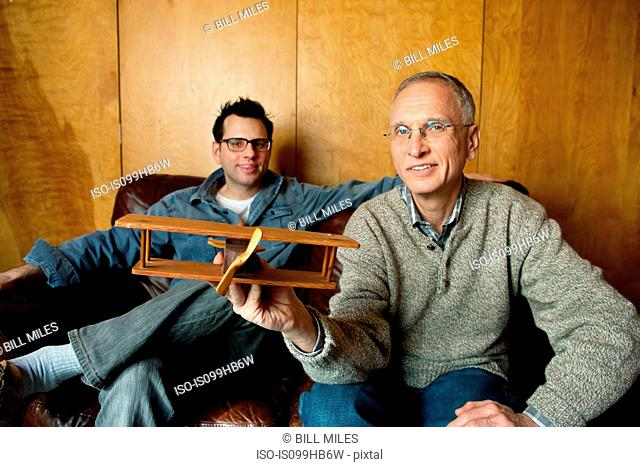 Father holding toy plane with adult son on couch, smiling