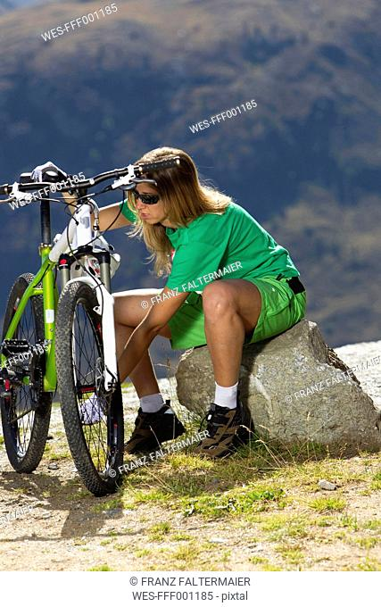 Italy, Livigno, View of woman sitting on rock besides mountain bike