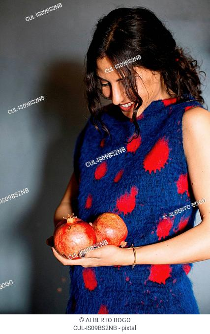 Young woman in red patterned dress holding pomegranates