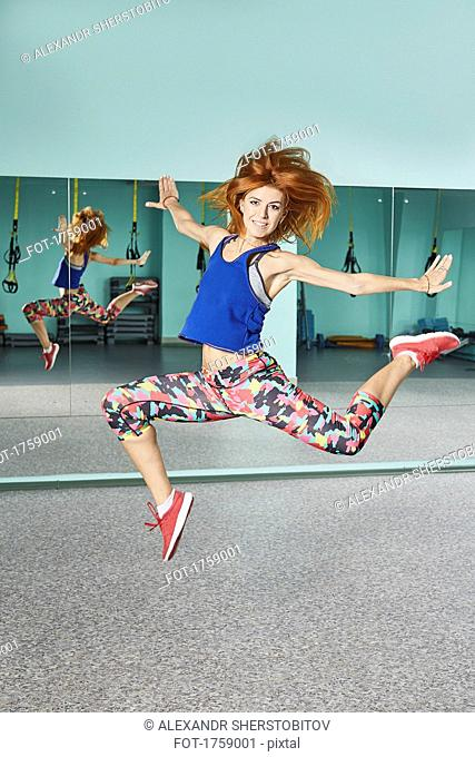 Full length portrait of young woman jumping in mid-air at health club