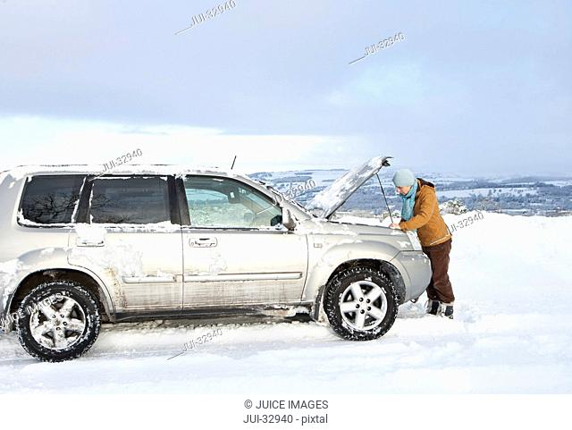 Woman standing in snow checking underneath car's hood