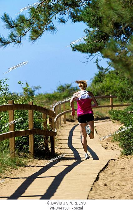 A jogger running along a boardwalk through a forest to the beach