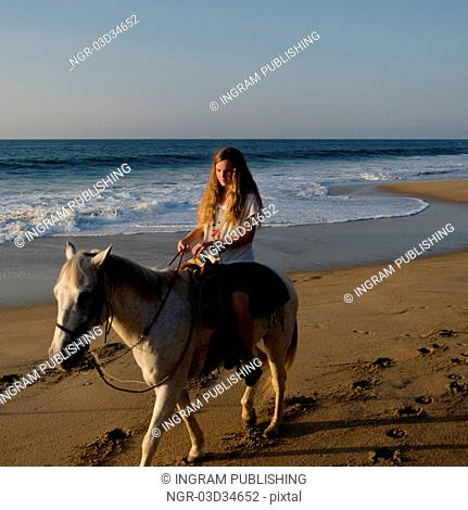 Teenage girl riding a horse on the beach, Sayulita, Nayarit, Mexico