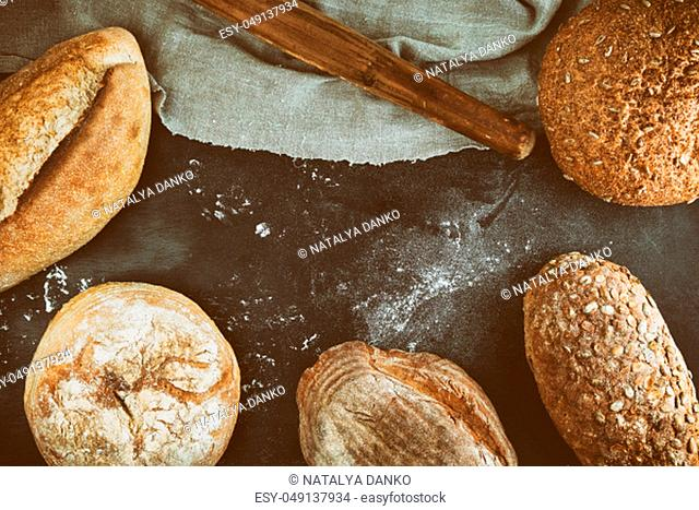 baked various loaves of bread on a black background, empty space in the middle, top view, vintage toning