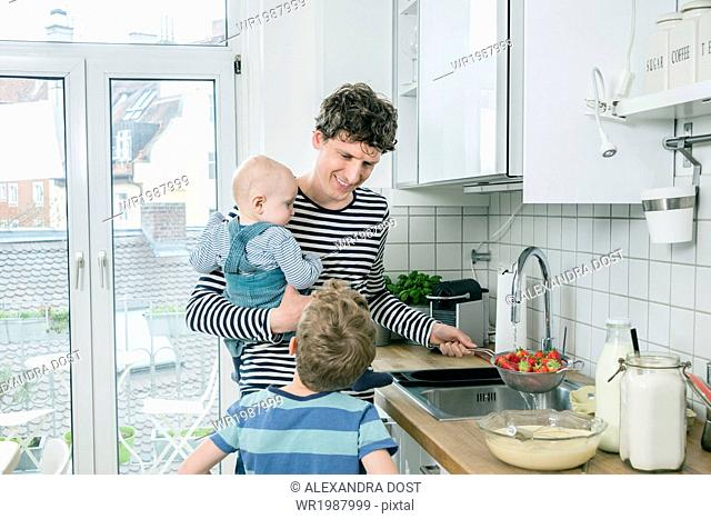 Father prepares food while holding baby in kitchen