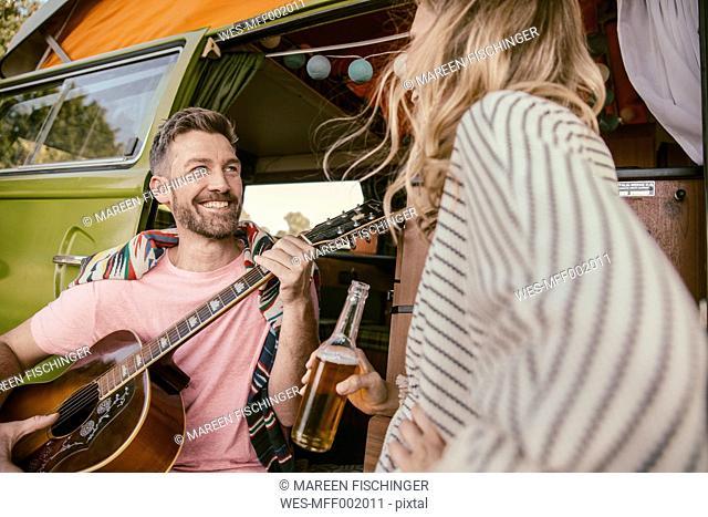 Happy couple in van making music