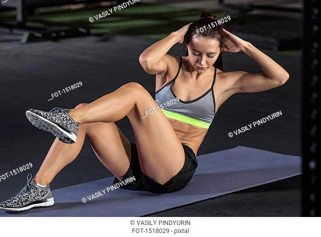 Young woman doing sit-ups on exercise mat at gym