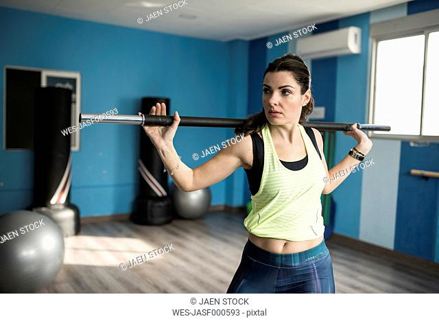 Mature woman training with fitness bar in gym