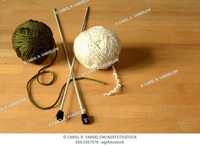 Two balls of wool (one dark green, one white) laying on table with knitting needles