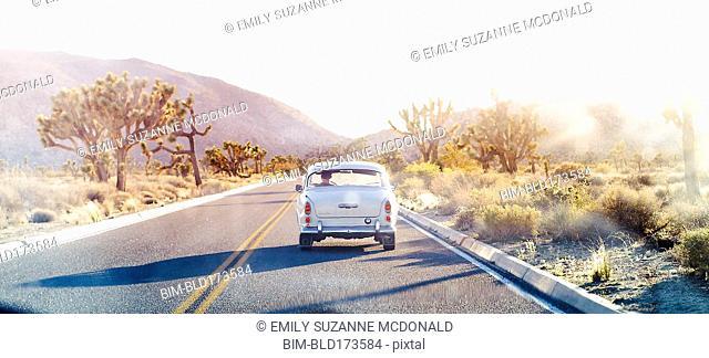 Vintage car driving on desert road