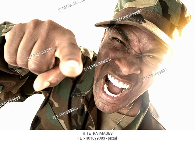Portrait of man wearing camouflage clothing, screaming and pointing towards camera