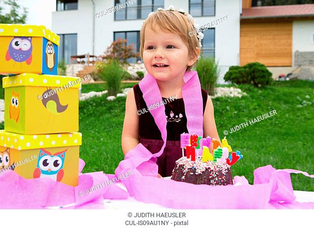 Portrait of female toddler with birthday cake and pink ribbons in garden