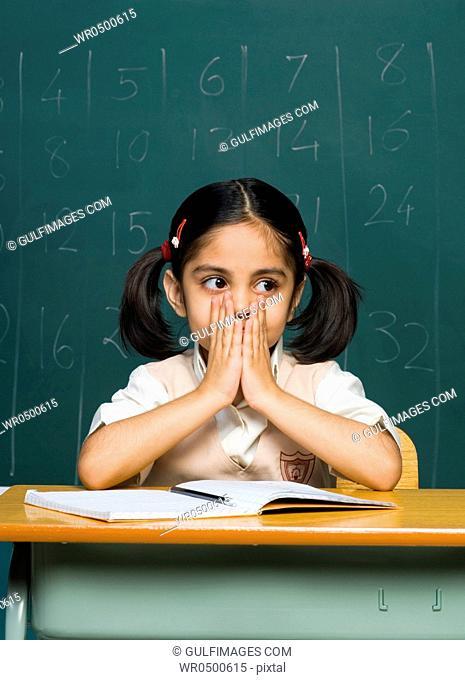 Girl 6-7 sitting on desk, contemplating