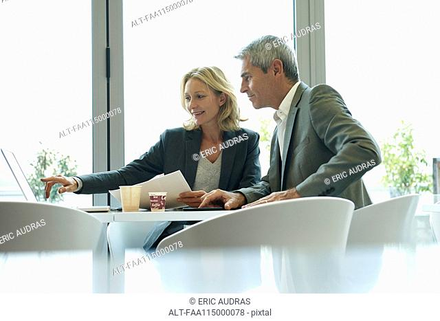 Businesspeople using laptop in cafeteria