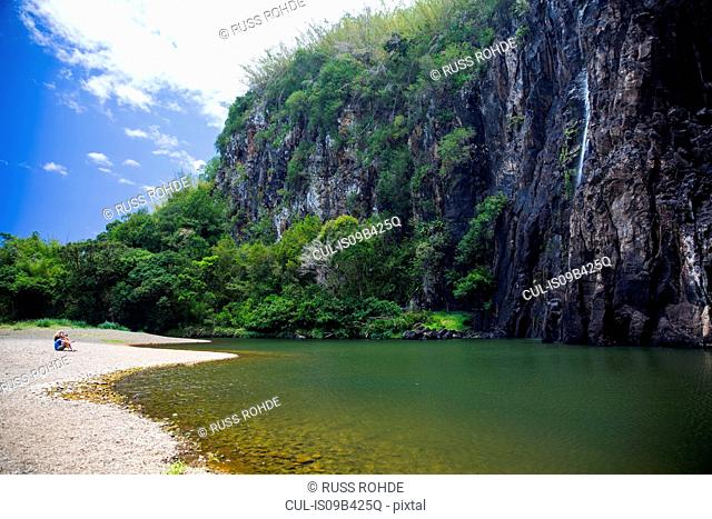 Couple sitting on tropical lakeside with rock waterfall, Reunion Island