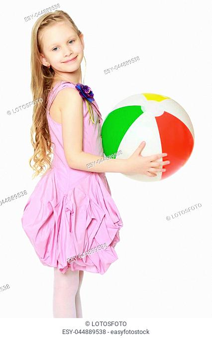 Happy little blond girl, with long curly hair, in a beautiful pink dress above the knees.She plays with a large multi-colored inflatable ball