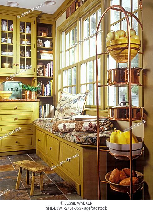 KITCHENS - Window seat area in remodeled kitchen, mustard colored cabinets, copper pot rack in foreground, built in book shelf for cookbooks