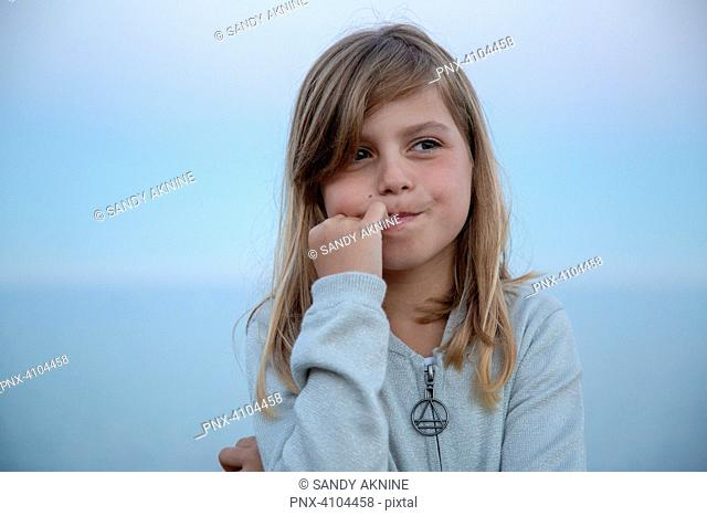 Portrait of an expressive pretty little girl who thinks in front of the sea at nightfall