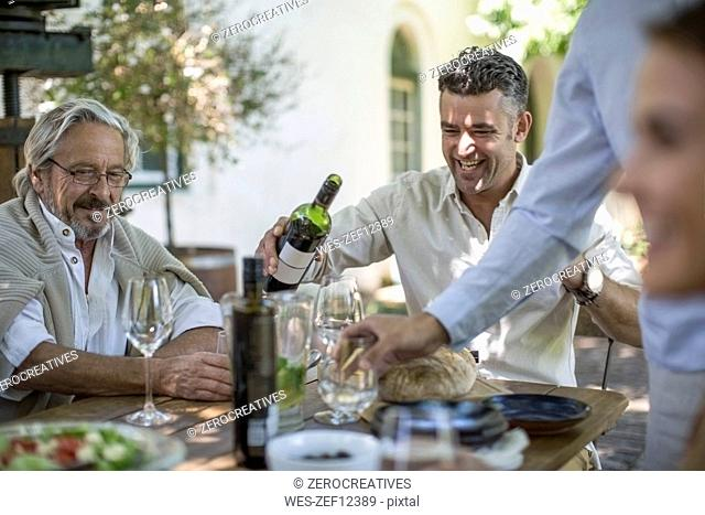 Father and son having wine enjoying family lunch together