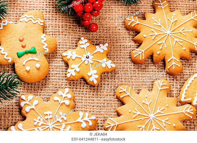 Christmas gingerbread cookies homemade with branches of Christmas tree and New Year decor on table with burlap tablecloth. Merry Christmas postcard