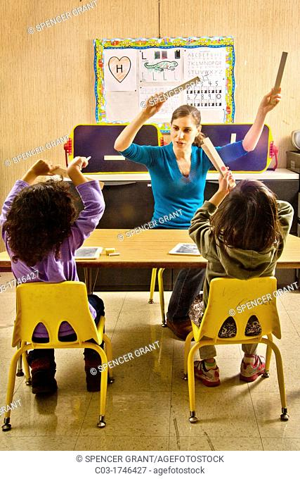 At the start of a in a special needs pre-Braille writing class at the Blind Children's Learning Center in Santa Ana, CA, a teacher adds movement by leading a...