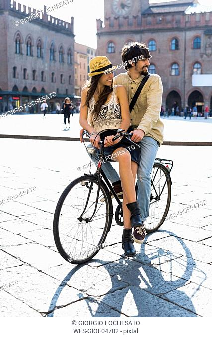 Italy, Bologna, young couple on bicycle watching something