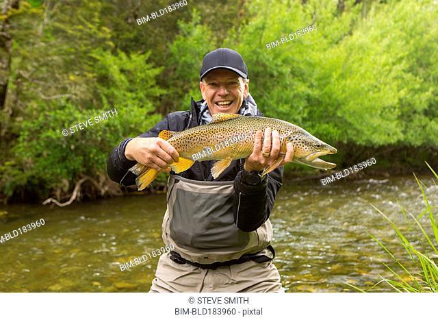 Caucasian man holding fish in remote river